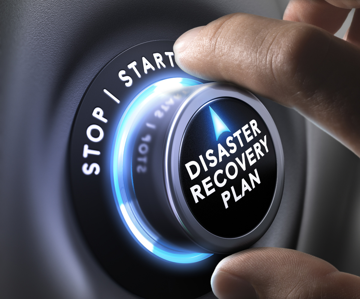 A hand turning a dial that says Disaster Recovery Plan 'from stop to start'