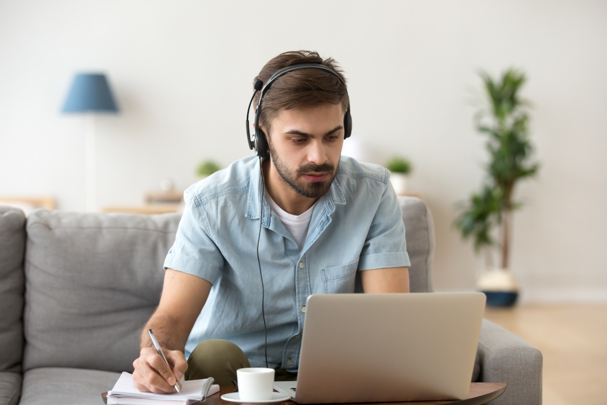 A man working from home on his laptop while wearing a headset with a mic and taking notes